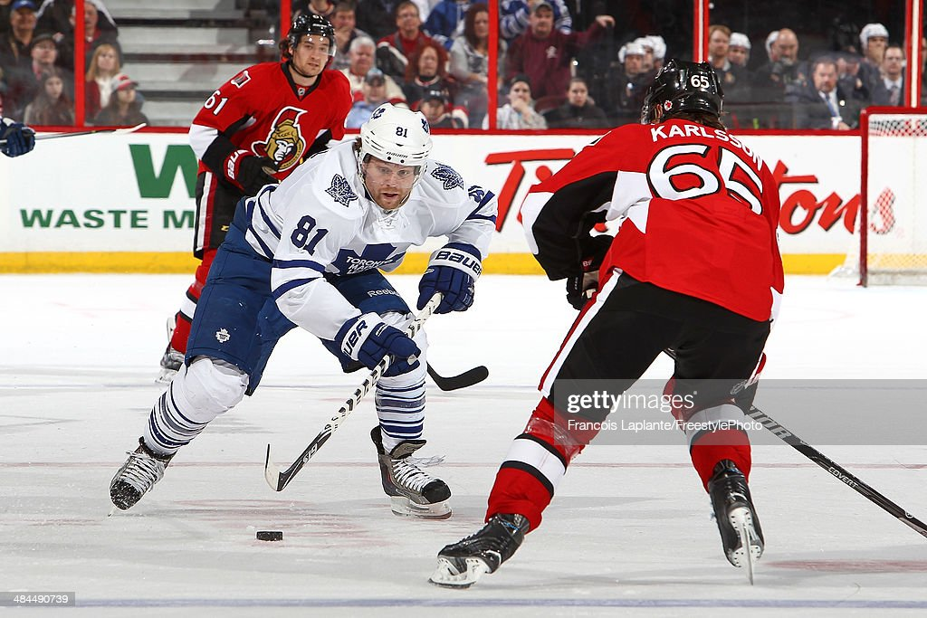 Phil Kessel #81 of the Toronto Maple Leafs skates with the puck against Erik Karlsson #65 of the Ottawa Senators on April 12, 2014 at Canadian Tire Centre in Ottawa, Ontario, Canada.