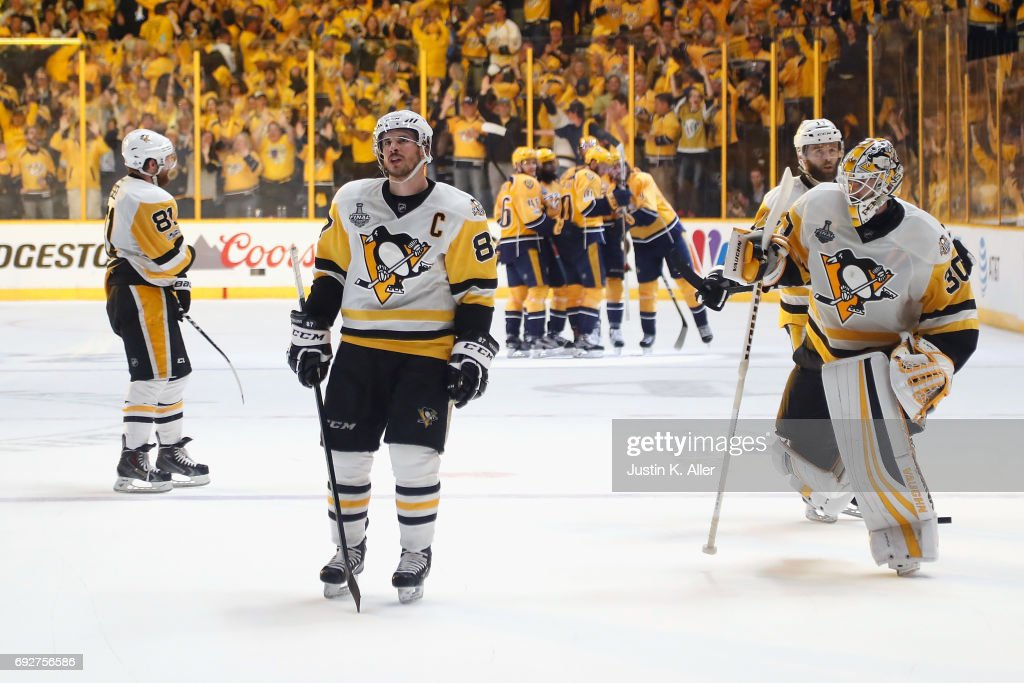 Phil Kessel #81, Sidney Crosby #87 and Matt Murray #30 of the Pittsburgh Penguins react as Filip Forsberg #9 of the Nashville Predators celebrates with his teammates after scoring an open net goal against the Pittsburgh Penguins during the third period in Game Four of the 2017 NHL Stanley Cup Final at the Bridgestone Arena on June 5, 2017 in Nashville, Tennessee.