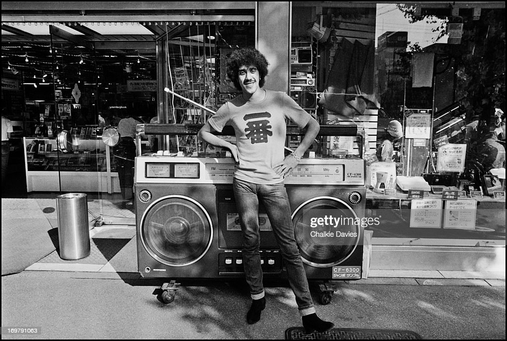 Phil Lynott of Thin Lizzy poses with a giant boombox outside an electronics store in Akihabara the electronics district of Tokyo on a day off during...
