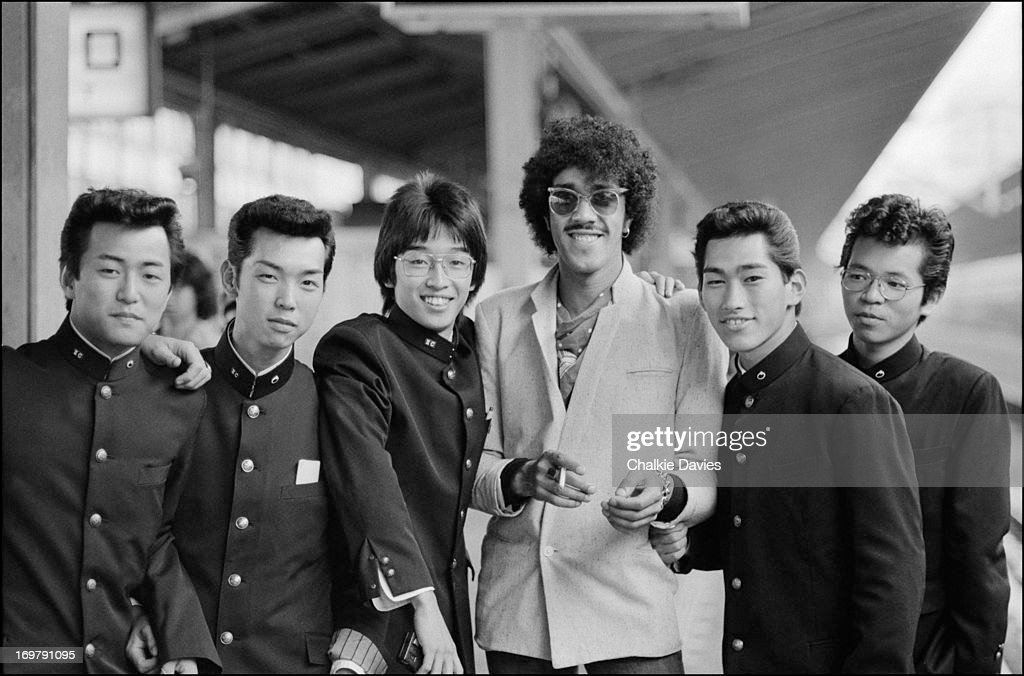 Phil Lynott of Thin Lizzy poses with five Japanese schoolboys on a railway platform in Tokyo whilst waiting for the Bullet Train to Osaka September...