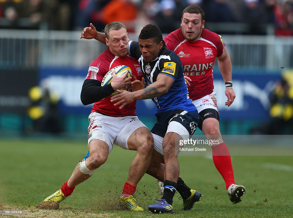 Phil Mackenzie (L) of London Welsh is held up by Kyle Eastmond (R) during the Aviva Premiership match between Bath and London Welsh at the Recreation Ground on March 30, 2013 in Bath, England.