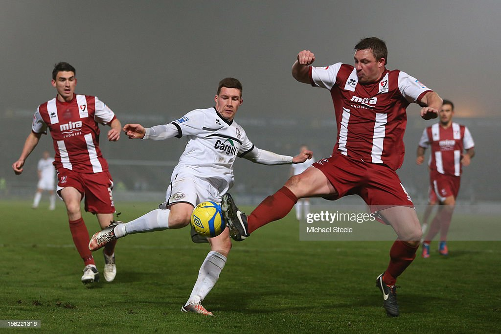 Phil Marsh (C) of Hereford United is challenged by Steve Elliott (R) of Cheltenham Town during the FA Cup with Budweiser Second Round Replay match between Hereford United and Cheltenham Town at Edgar Street Athletic Ground on December 11, 2012 in Hereford, England.