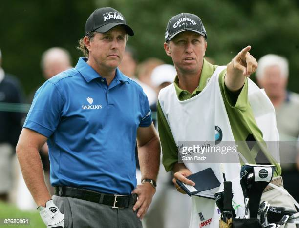 Phil Mickelosn and caddie Jim MacKay chat on the first tee during the rain delayed first round of the BMW Championship held at Bellerive Country Club...