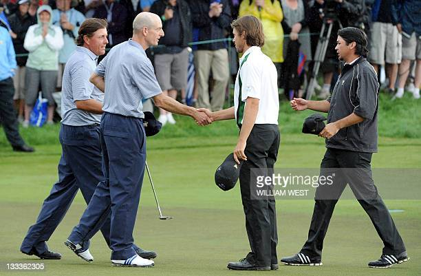 Phil Mickelson and Jim Furyk of the US are congratulated by International team members Australians Aaron Baddeley and Jason Day after winning their...