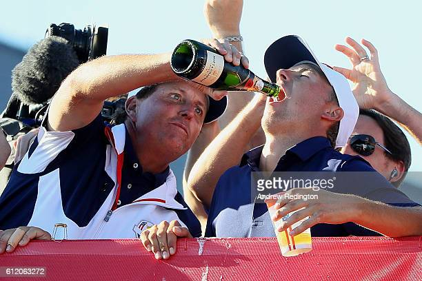 Phil Mickelson and Jordan Spieth of the United States celebrate with champagne after winning the Ryder Cup during singles matches of the 2016 Ryder...