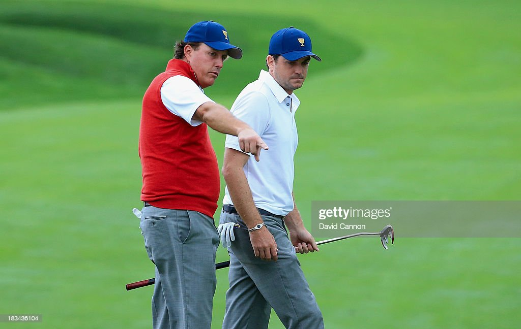 Phil Mickelson and Keegan Bradley of the U.S. Team look over a shot on the 18th hole during the weather-delayed Day Three Foursome Matches at the Muirfield Village Golf Club on October 6, 2013 in Dublin, Ohio.