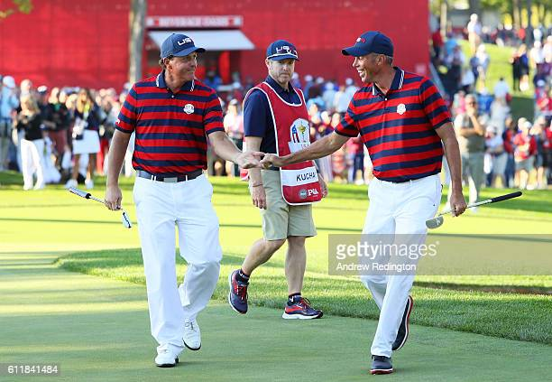 Phil Mickelson and Matt Kuchar of the United States reacts after a putt by Kuchar on the 13th green during afternoon fourball matches of the 2016...
