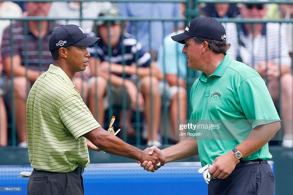 Phil Mickelson and Tiger Woods shake hands before the beginning of the first round of Deutsche Bank Championship the second event of the new PGA TOUR...