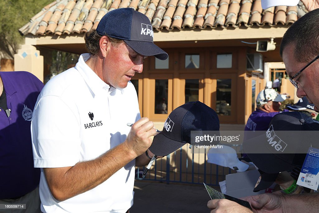 Phil Mickelson autographs a blue KPMG hat for a fan after the third round of the Waste Management Phoenix Open at TPC Scottsdale on February 2, 2013 in Scottsdale, Arizona.