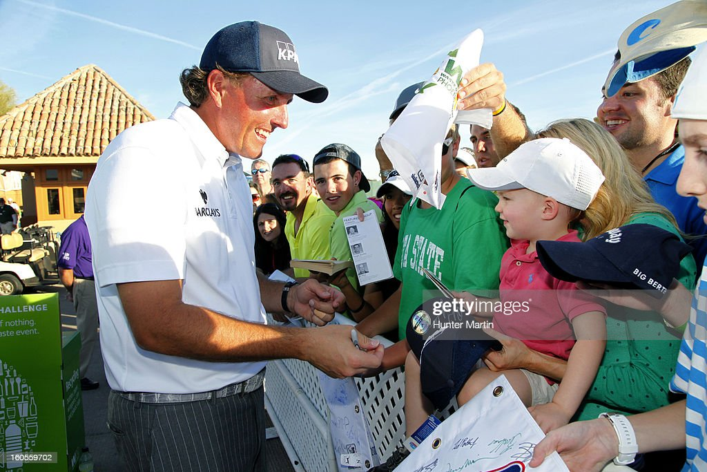 Phil Mickelson autographs a blue KPMG hat for a young fan after the third round of the Waste Management Phoenix Open at TPC Scottsdale on February 2, 2013 in Scottsdale, Arizona.