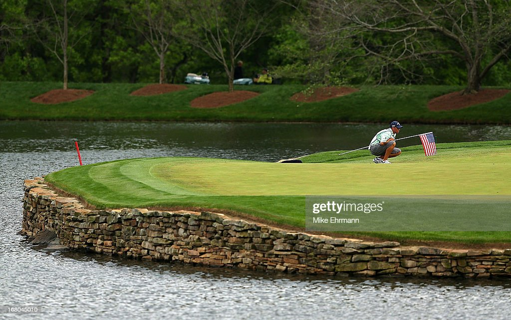 Phil Mickelson caddy Jim Mackay lines up a putt on the 17th hole during the third round of the Wells Fargo Championship at Quail Hollow Club on May 4, 2013 in Charlotte, North Carolina.