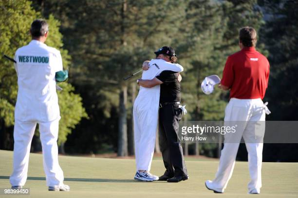 Phil Mickelson celebrates his threestroke victory with his caddie Jim Mackay as Lee Westwood of England and his caddie Billy Foster look on during...