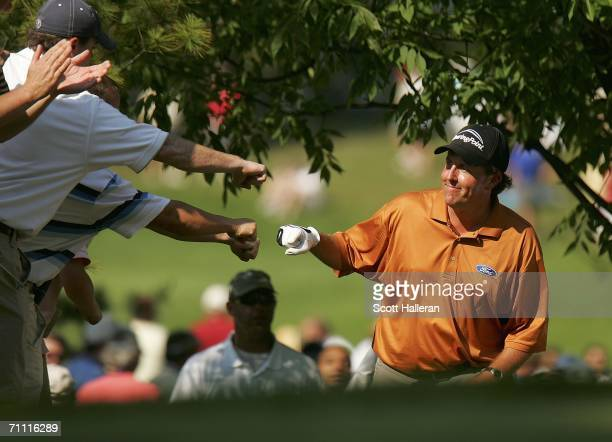 Phil Mickelson celebrates with fans after an eagle putt on the seventh hole during the third round of the The Memorial Tournament at the Muirfield...