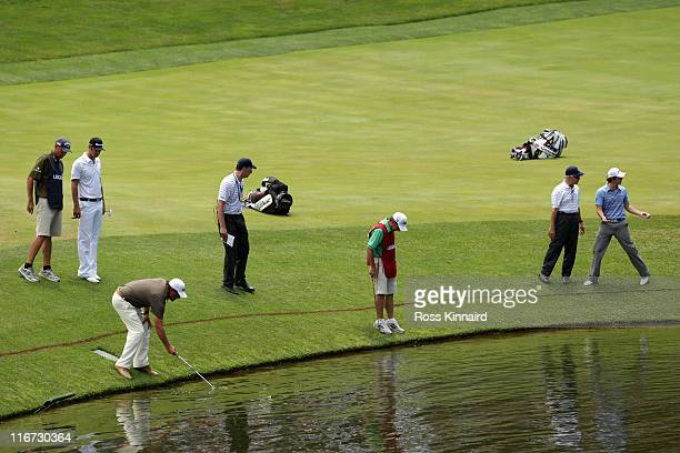 Phil Mickelson collects his golf ball from the water on the 18th hole as Rory McIlroy of Northern Ireland looks to take a drop during the second...