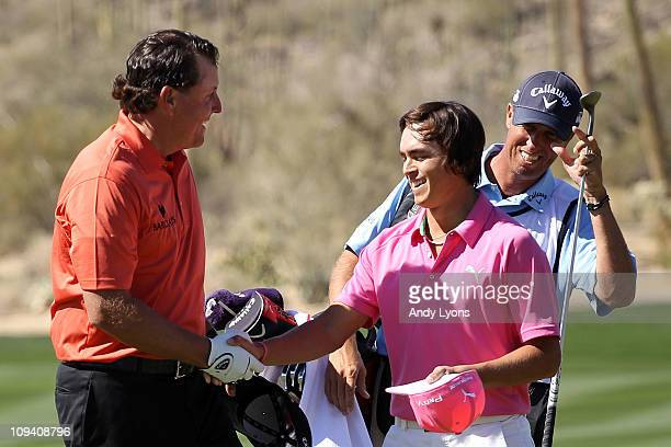 Phil Mickelson congrulates Rickie Fowler on his win on the 13th hole as caddie Jim 'Bones' Mackay looks on during the second round of the Accenture...