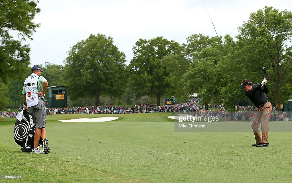Phil Mickelson hits his approach shot on the 14th hole during the third round of the Wells Fargo Championship at Quail Hollow Club on May 4, 2013 in Charlotte, North Carolina.