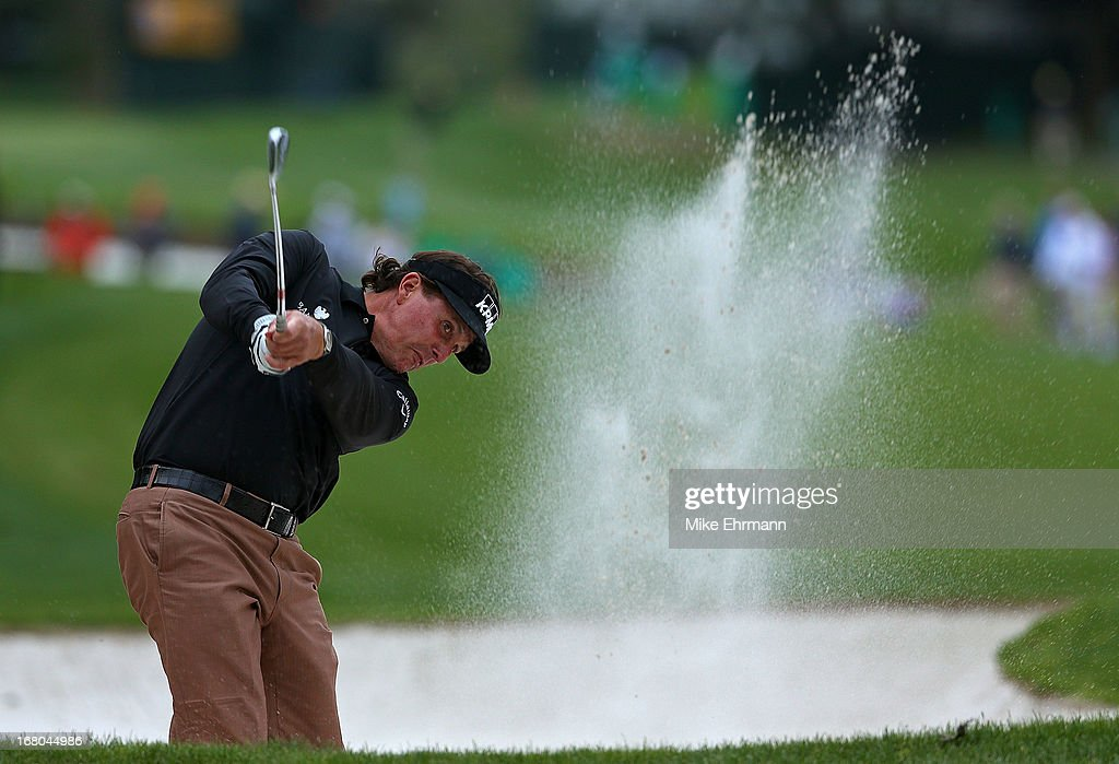 Phil Mickelson hits his shot out of the bunker on the 18th hole during the third round of the Wells Fargo Championship at Quail Hollow Club on May 4, 2013 in Charlotte, North Carolina.