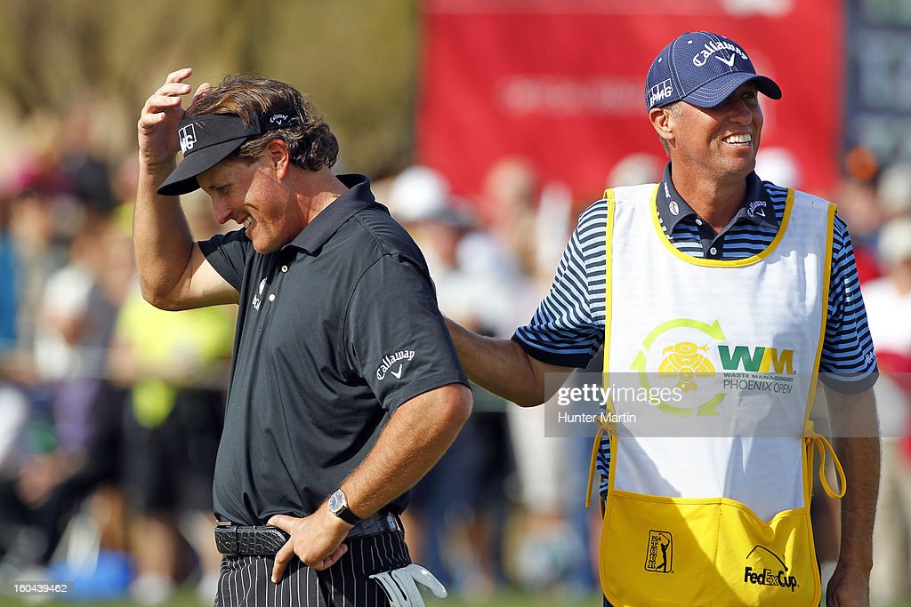 Phil Mickelson is consoled by his caddie Jim Mackay after missing his birdie putt on the ninth hole that would have given him a round of 59 during the first round of the Waste Management Phoenix Open at TPC Scottsdale on January 31, 2013 in Scottsdale, Arizona.