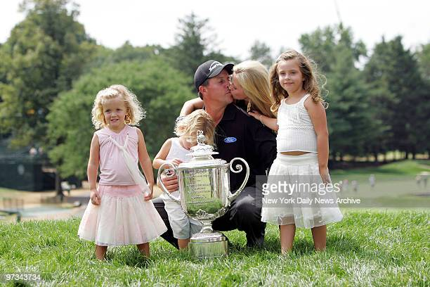 Phil Mickelson kisses his wife Amy as they celebrate with their children Sophia Evan and Amanda after he won the 87th PGA Championship at Baltusrol...