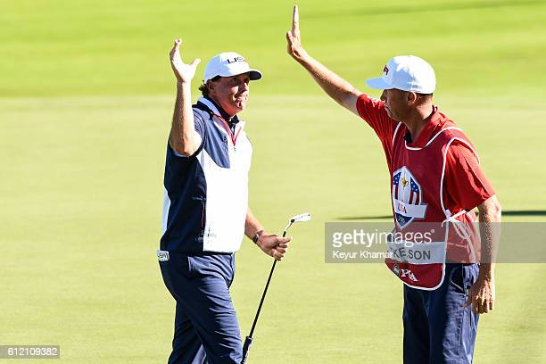 Phil Mickelson of Team USA celebrates with caddie Jim 'Bones' Mackay on the 18th hole green after making a birdie putt during singles matches of the...