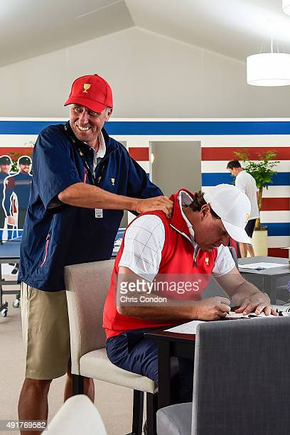 Phil Mickelson of Team USA gets a neckrub from his caddie Jim 'Bones' Mackay in the team cabin during the first round of The Presidents Cup at Jack...