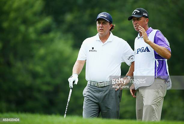 Phil Mickelson of the United States and caddie Jim 'Bones' Mackay talk on the fourth hole tee during the third round of the 96th PGA Championship at...