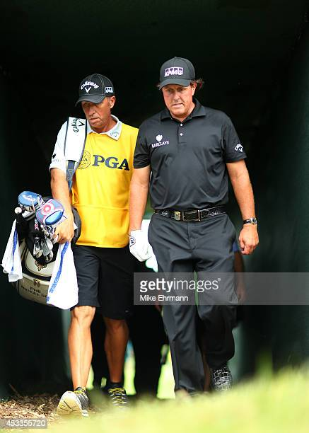 Phil Mickelson of the United States and caddie Jim 'Bones' Mackay walk through the tunnel to the 18th hole during the second round of the 96th PGA...