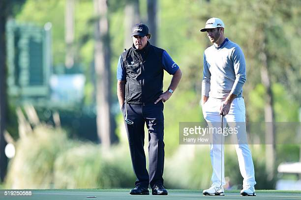 Phil Mickelson of the United States and Dustin Johnson of the United States prepare to putt during a practice round prior to the start of the 2016...