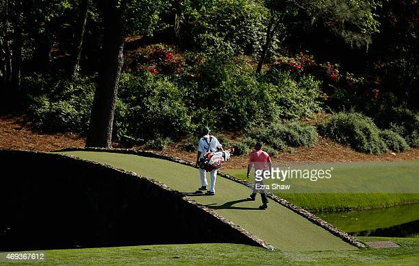 Phil Mickelson of the United States and his caddie Jim Mackay cross the Hogan Bridge during the third round of the 2015 Masters Tournament at Augusta...