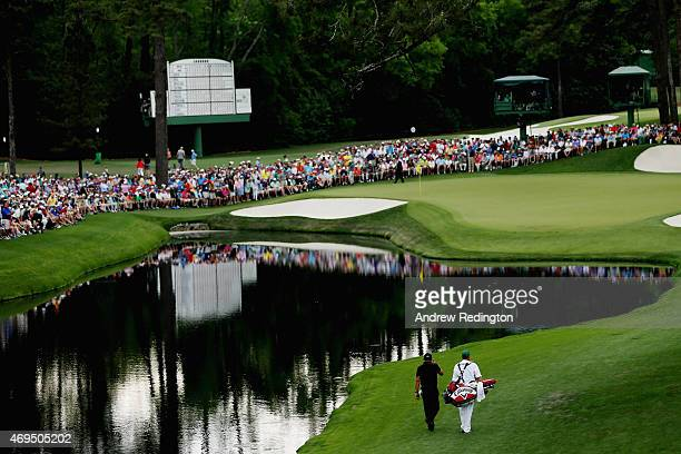Phil Mickelson of the United States and his caddie Jim Mackay walk to the 16th green during the final round of the 2015 Masters Tournament at Augusta...