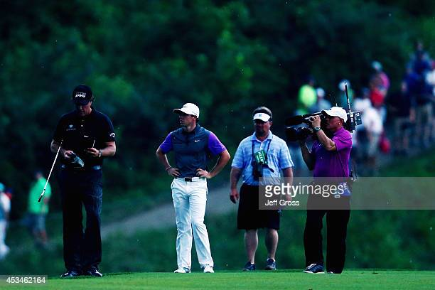 Phil Mickelson of the United States and Rory McIlroy of Northern Ireland wait in the 18th fairway during the final round of the 96th PGA Championship...