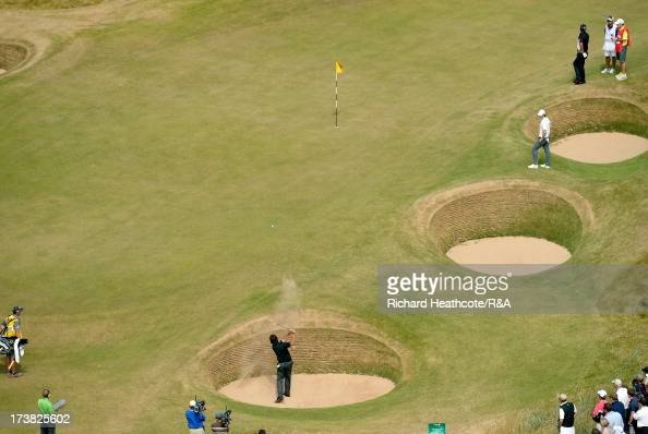 Phil Mickelson of the United States hits from a bunker on the 13th hole as Rory McIlroy of Northern Ireland looks on during the first round of the...
