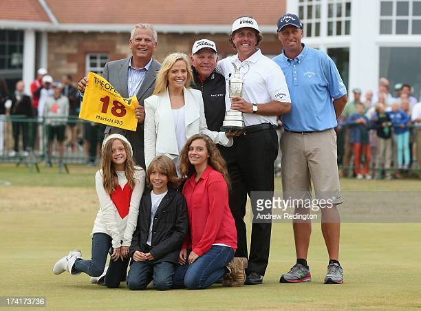 Phil Mickelson of the United States holds the Claret Jug wife Amy and children Evan Amanda and Sophia manager Steve Loy coach Butch Harmon and caddie...
