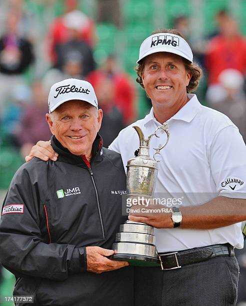 Phil Mickelson of the United States holds the Claret Jug with his coach Butch Harmon after winning the 142nd Open Championship at Muirfield on July...