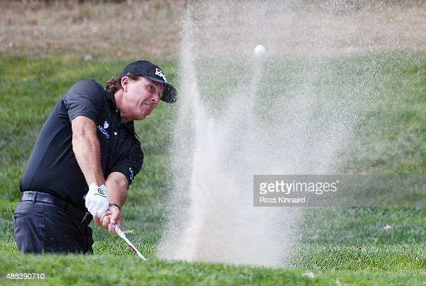 Phil Mickelson of the United States plays a bunker shot on the fifth hole during the first round of The Barclays at Plainfield Country Club on August...