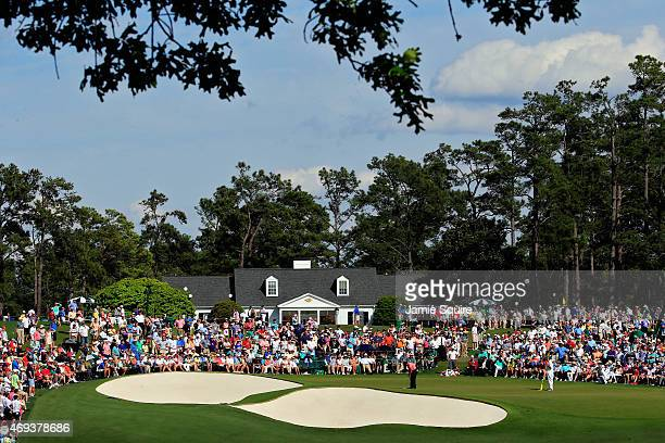 Phil Mickelson of the United States putts on the ninth green as a gallery of patrons look on during the third round of the 2015 Masters Tournament at...