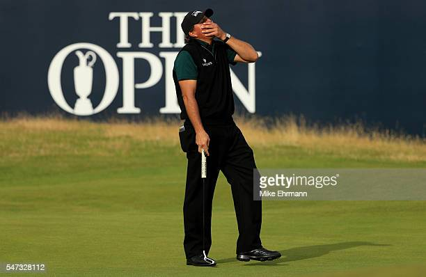 Phil Mickelson of the United States reacts after his birdie putt narrowly missed the hole on the 18th during the first round on day one of the 145th...