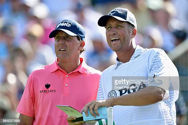 Phil Mickelson of the United States talks with caddie Jim 'Bones' Mackay on the 13th tee during the first round of the 2016 PGA Championship at...