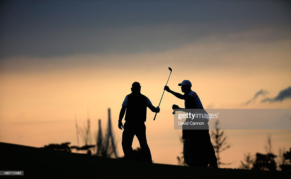 Phil Mickelson of the United States team and his caddie Jim Mackay on the 15th fairway as the sun sets during the Saturday afternoon fourball matches...