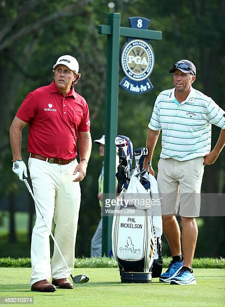 Phil Mickelson of the United States waits on the eighth tee alongside caddie Jim 'Bones' Mackay during a practice round prior to the start of the...