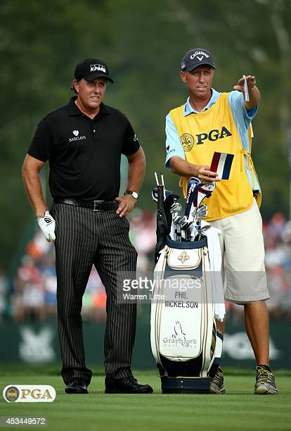 Phil Mickelson of the United States waits to hit his tee shot on the fifth hole alongside caddie Jim 'Bones' Mackay during the final round of the...