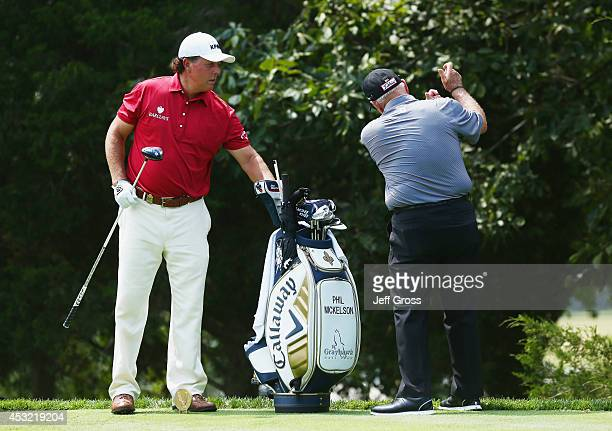 Phil Mickelson of the United States works with his coach Butch Harmon during a practice round prior to the start of the 96th PGA Championship at...