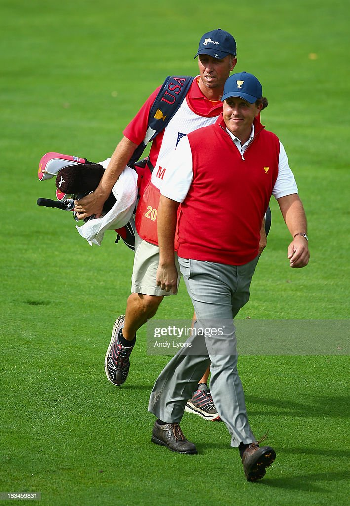 Phil Mickelson of the U.S. Team and his caddie Jim Mackay walk up the fairway of the 18th hole during the Day Four Singles Matches at the Muirfield Village Golf Club on October 6, 2013 in Dublin, Ohio.