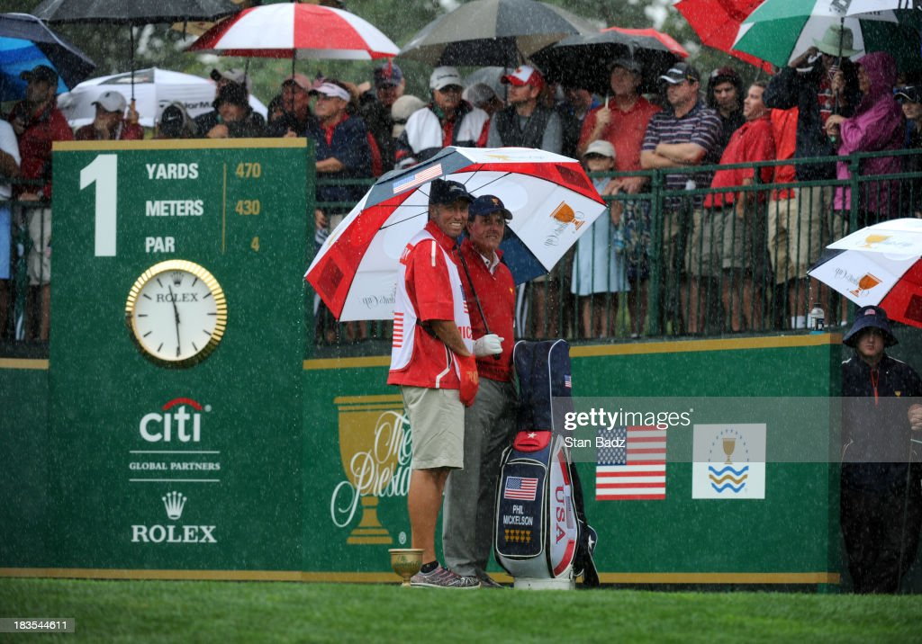 Phil Mickelson of the U.S. Team and Jim Mackay shelter from the rain on the first hole during the Final Round Singles Matches of The Presidents Cup at the Muirfield Village Golf Club on October 6, 2013 in Dublin, Ohio.