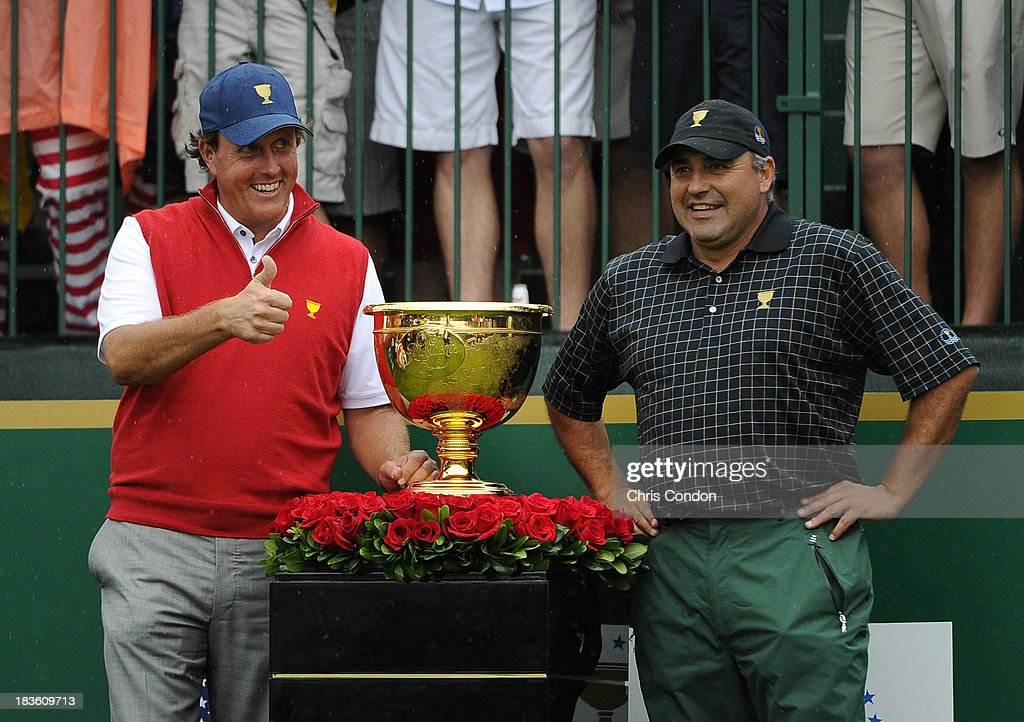 Phil Mickelson of the U.S. Team gives a thumbs-up to the fans as he pose for a photo with Angel Cabrera of the International Team on the first hole during the Final Round Singles Matches of The Presidents Cup at the Muirfield Village Golf Club on October 6, 2013 in Dublin, Ohio.