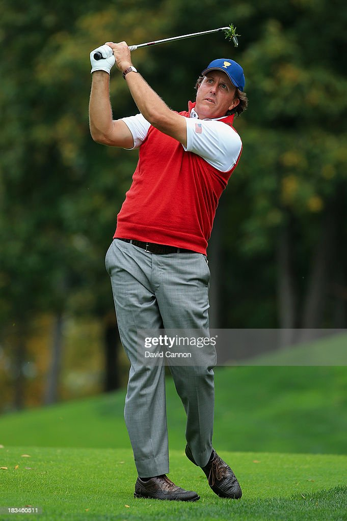 Phil Mickelson of the U.S. Team hits his second shot on the ninth hole as his caddie, Angel Cabrera Jr., looks on during the Day Four Singles Matches at the Muirfield Village Golf Club on October 6, 2013 in Dublin, Ohio.