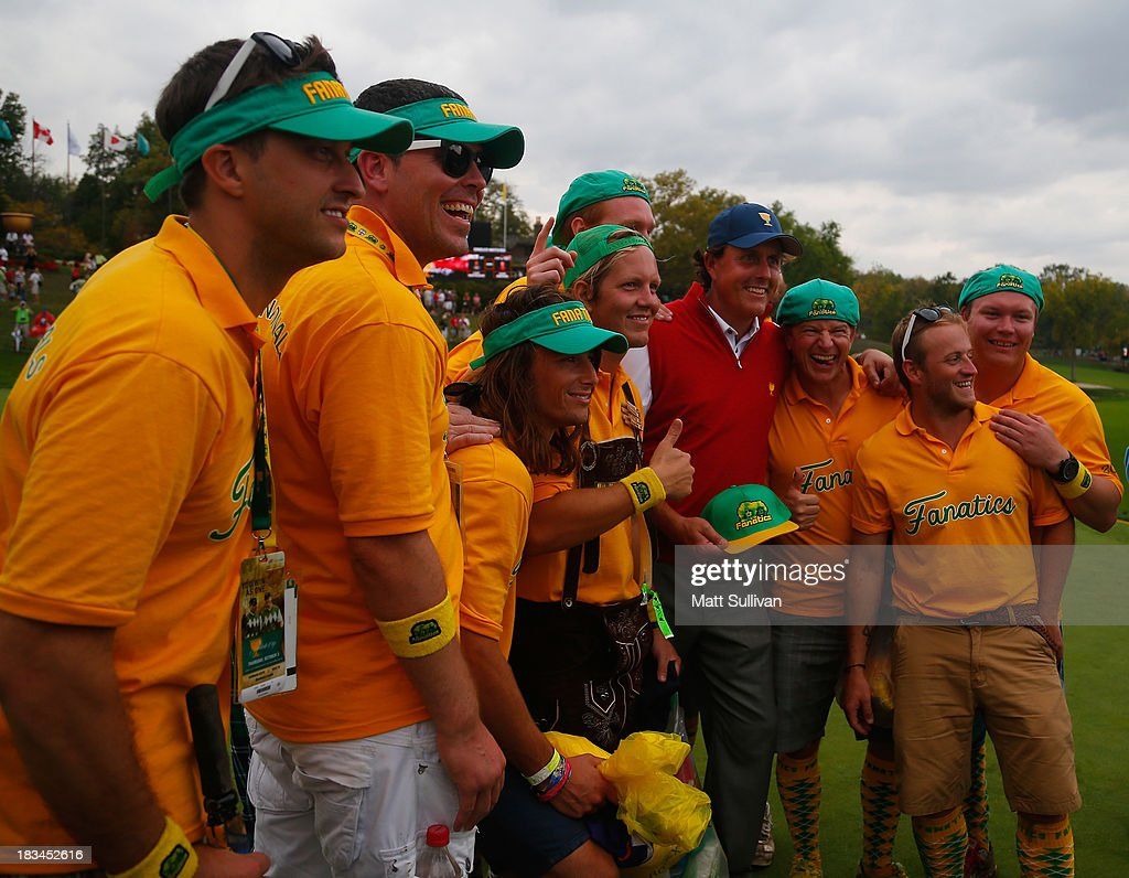 Phil Mickelson of the U.S. Team poses for a picture with International Team supporters on the 18th greeen during the Day Four Singles Matches at the Muirfield Village Golf Club on October 6, 2013 in Dublin, Ohio.