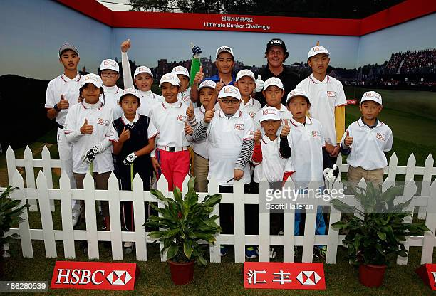 Phil Mickelson of the USA and Liang Wenchong of China pose with the young golfers during a China Golf Association junior clinic following the proam...