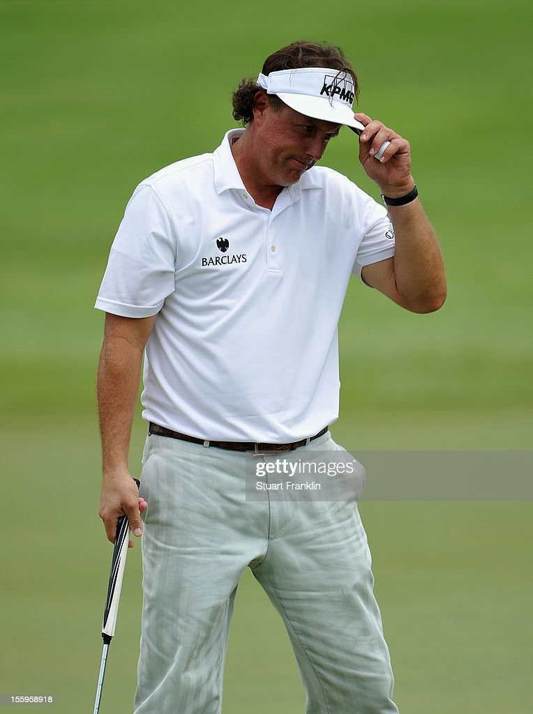 Phil Mickelson of USA doffs his cap on the 18th hole during the resumption of the rain delayed second round of the Barclays Singapore Open at the Sentosa Golf Club on November 10, 2012 in Singapore.
