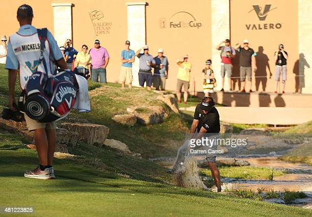 Phil Mickelson plays a shot out of the creek on the 18th during Round Two of the Valero Texas Open at TPC San Antonio ATT Oaks Courseon March 28 2014...